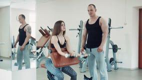 Γυναίκα που κάνει την άσκηση δικέφαλων μυών με τους αλτήρες απόθεμα βίντεο
