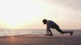 Γυναίκα που κάνει την ικανότητα workout στο ηλιοβασίλεμα θαλασσίως απόθεμα βίντεο