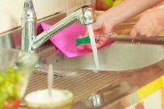 Γυναίκα που κάνει την πλύση επάνω στην κουζίνα Στοκ Φωτογραφίες