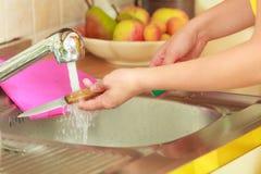 Γυναίκα που κάνει την πλύση επάνω στην κουζίνα Στοκ φωτογραφία με δικαίωμα ελεύθερης χρήσης