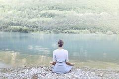 Γυναίκα που κάνει τη γιόγκα μπροστά από μια θεαματική λίμνη βουνών Στοκ φωτογραφίες με δικαίωμα ελεύθερης χρήσης