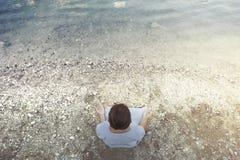 Γυναίκα που κάνει τη γιόγκα μπροστά από μια θεαματική λίμνη βουνών Στοκ Εικόνες