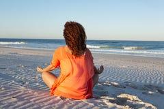 Γυναίκα που κάνει τη γιόγκα στην παραλία στην ηλιοφάνεια στοκ εικόνες