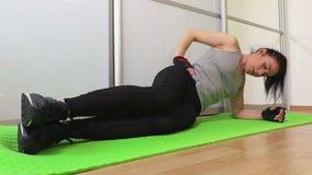 Γυναίκα που κάνει τη δευτερεύουσα σανίδα άσκησης πυρήνων απόθεμα βίντεο