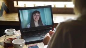 Γυναίκα που κάνει τη σε απευθείας σύνδεση τηλεοπτική κλήση που χρησιμοποιεί το lap-top φιλμ μικρού μήκους