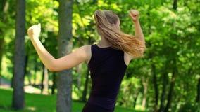 Γυναίκα που κάνει τις ασκήσεις ικανότητας στο πράσινο πάρκο στην άνοιξη Θηλυκή προθέρμανση δρομέων απόθεμα βίντεο