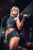 Γυναίκα που κάνει τις ασκήσεις με τον αλτήρα στη γυμναστική Στοκ εικόνα με δικαίωμα ελεύθερης χρήσης