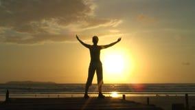 Γυναίκα που κάνει τις ασκήσεις χαλάρωσης στην ανατολή απόθεμα βίντεο