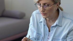 Γυναίκα που κάνει τις σημειώσεις στο σημειωματάριο που ακούει προσεκτικά τις σε απευθείας σύνδεση κατηγορίες, self-development απόθεμα βίντεο