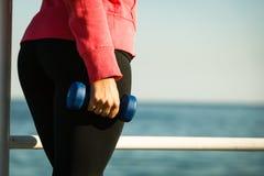 Γυναίκα που κάνει τον αθλητισμό υπαίθρια με τους αλτήρες Στοκ Φωτογραφία