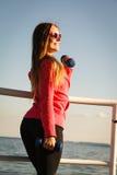 Γυναίκα που κάνει τον αθλητισμό υπαίθρια με τους αλτήρες Στοκ φωτογραφία με δικαίωμα ελεύθερης χρήσης