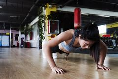 Γυναίκα που κάνει το ώθηση-UPS σε μια γυμναστική στοκ φωτογραφία