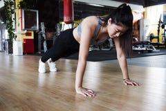 Γυναίκα που κάνει το ώθηση-UPS σε μια γυμναστική στοκ φωτογραφία με δικαίωμα ελεύθερης χρήσης