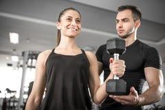 Γυναίκα που κάνει bicep τις μπούκλες στη γυμναστική με τον προσωπικό εκπαιδευτή της στοκ φωτογραφίες