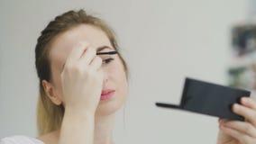 Γυναίκα που κάνει makeup των ματιών από μαύρο mascara, εξετάζοντας τον καθρέφτη φιλμ μικρού μήκους
