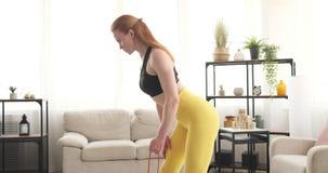 Γυναίκα που κάνει triceps την άσκηση που χρησιμοποιεί τη ζώνη αντίστασης απόθεμα βίντεο