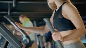 Γυναίκα που κάνει workout στο orbitrek στη γυμναστική απόθεμα βίντεο