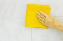 Καθαρίζοντας κεραμίδια γυναικών με το κίτρινο ύφασμα Στοκ εικόνα με δικαίωμα ελεύθερης χρήσης