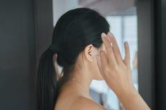 Γυναίκα που καθαρίζει τα αυτιά της με τον οφθαλμό βαμβακιού στην κρεβατοκάμαρα, θηλυκό που χρησιμοποιεί το ραβδί βαμβακιού Στοκ Εικόνα