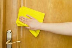 Καθαρισμός της ξύλινης πόρτας με ένα κίτρινο ύφασμα Στοκ Φωτογραφία