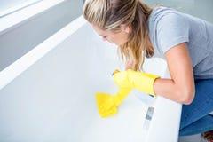 Γυναίκα που καθαρίζει τη σκάφη λουτρών στοκ εικόνες