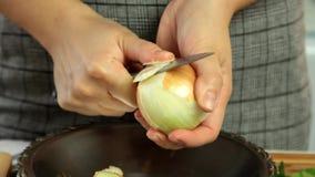 Γυναίκα που καθαρίζει το άσπρο κρεμμύδι με το μεγάλο μαχαίρι απόθεμα βίντεο