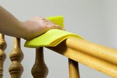 Γυναίκα που καθαρίζει το ξύλινο κιγκλίδωμα Στοκ φωτογραφία με δικαίωμα ελεύθερης χρήσης