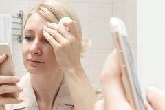 Γυναίκα που καθαρίζει το πρόσωπό της με ένα μαξιλάρι βαμβακιού και που προσέχει ένα smartphone στο χέρι της Έννοια εθισμού Διαδικ στοκ εικόνα με δικαίωμα ελεύθερης χρήσης
