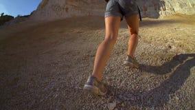 Γυναίκα που και που αναρριχείται Η ισχυρή καθορισμένη γυναίκα τουριστών αναρριχείται στο βράχο στα ηλιόλουστα βουνά Σε αργή κίνησ απόθεμα βίντεο