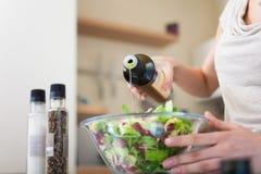 Γυναίκα που καρυκεύει μια σαλάτα Στοκ Εικόνες