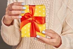 Γυναίκα που καταδεικνύει ένα κιβώτιο δώρων Στοκ Εικόνες