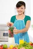 Γυναίκα που κατασκευάζει έναν φρέσκο χυμό στοκ εικόνες