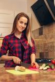 Γυναίκα που κατασκευάζει τη σαλάτα με την ντομάτα στην κουζίνα Στοκ Εικόνες