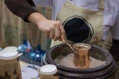 Γυναίκα που κατασκευάζει τον καφέ στο jezva στην καυτή άμμο στην ειδική θερμάστρα στοκ εικόνα