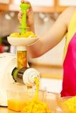 Γυναίκα που κατασκευάζει το χυμό από πορτοκάλι στη μηχανή juicer Στοκ φωτογραφίες με δικαίωμα ελεύθερης χρήσης
