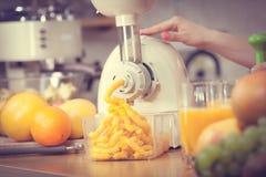 Γυναίκα που κατασκευάζει το χυμό από πορτοκάλι στη μηχανή juicer Στοκ Φωτογραφία