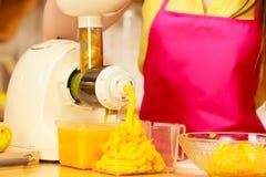 Γυναίκα που κατασκευάζει το χυμό από πορτοκάλι στη μηχανή juicer Στοκ Εικόνα