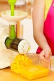 Γυναίκα που κατασκευάζει το χυμό από πορτοκάλι στη μηχανή juicer Στοκ Εικόνες