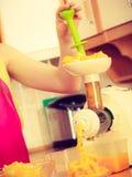 Γυναίκα που κατασκευάζει το χυμό από πορτοκάλι στη μηχανή juicer Στοκ Φωτογραφίες