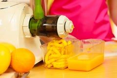 Γυναίκα που κατασκευάζει το χυμό από πορτοκάλι στη μηχανή juicer Στοκ φωτογραφία με δικαίωμα ελεύθερης χρήσης