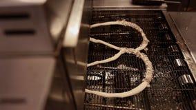 Γυναίκα που κατασκευάζει φρέσκα pretzels με τους σπόρους ηλίανθων και σουσαμιού στο αρτοποιείο φιλμ μικρού μήκους