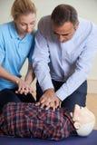 Γυναίκα που καταδεικνύει CPR στο ομοίωμα κατάρτισης στην κατηγορία πρώτων βοηθειών Στοκ Εικόνα