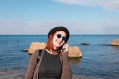 Γυναίκα που καλεί με τηλέφωνο κυττάρων και που περπατά στην παραλία Στοκ Φωτογραφίες