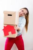 Γυναίκα που κινείται στο σπίτι με τα κιβώτια και το σπίτι εγγράφου στοκ εικόνα με δικαίωμα ελεύθερης χρήσης