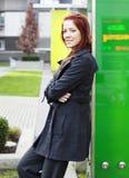 Γυναίκα που κλίνει ενάντια στο αντανακλαστικό πράσινο γυαλί Στοκ εικόνα με δικαίωμα ελεύθερης χρήσης