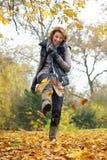 Γυναίκα που κλωτσά τα κίτρινα φύλλα το φθινόπωρο στοκ εικόνες