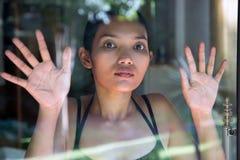 Γυναίκα που κοιτάζει έξω μέσω του παραθύρου στοκ εικόνα
