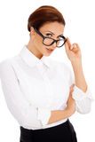 Γυναίκα που κοιτάζει αδιάκριτα πέρα από τα γυαλιά της Στοκ εικόνα με δικαίωμα ελεύθερης χρήσης