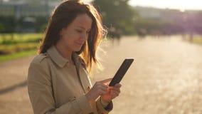 Γυναίκα που κοιτάζει βιαστικά στο smartphone, πορτρέτο ενάντια στο φως του ήλιου απόθεμα βίντεο