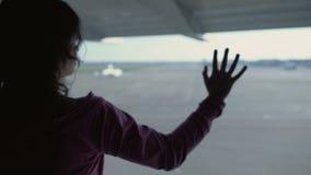 Γυναίκα που κοιτάζει δυστυχώς μέσω του παραθύρου αερολιμένων, ελλείπον σπίτι, νοσταλγία αναχώρησης απόθεμα βίντεο